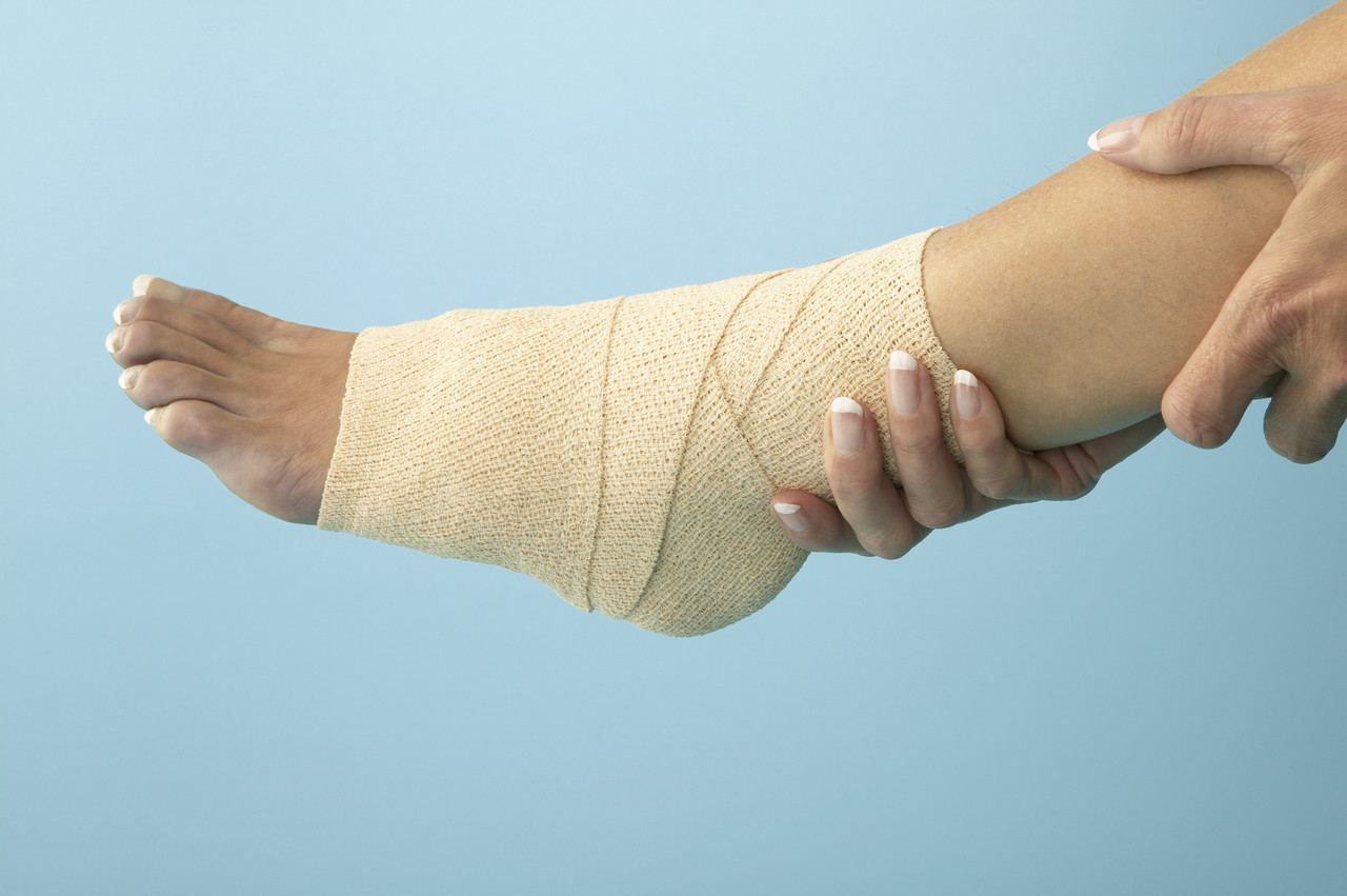 Woman Holding Bandaged Ankle
