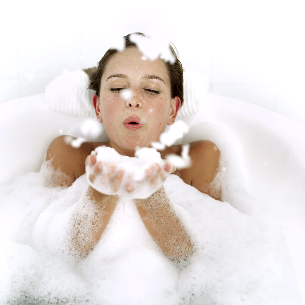 Young Woman in a Bathtub Blowing Foam from Her Hands