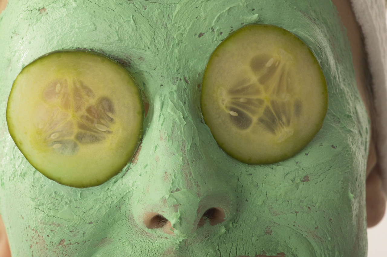 Young Woman Wearing Facial Cream and Cucumber Slices Over Eyes